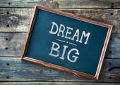 Hand drawn chalkboard sign DREAM BIG over old wooden table backg — Stock Photo