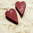 Two wooden red hearts on the sand — Stock Photo #63317875