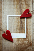 Two red heart shaped valentine's  on the rustic wooden background with polaroid frame — Stock Photo