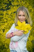 Blond woman with blue eyes in light shirt in autumn forest — Stock Photo