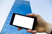 Mobile phone in front of the office building — Stock Photo