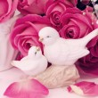 Figurines wedding doves in love Valentine bouquet of pink roses on old books floral background is love tenderness vintage retro selective soft focus — Stock Photo #74238191
