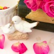 Figurines wedding doves in love Valentine bouquet of pink roses on old books floral background is love tenderness vintage retro selective soft focus — Stock Photo #74238271