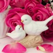 Figurines wedding doves in love Valentine bouquet of pink roses on old books floral background is love tenderness vintage retro selective soft focus — Stock Photo #74238275