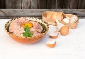 Kip gemalen vlees voor gehaktballen ui knoflook eieren hout backgro — Stockfoto