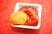 A Bowl of Catsup with a Chicken or Fish Nugget Over Red — Stock Photo