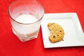 Napůl snědený cookie s téměř prázdnou sklenici mléka — Stock fotografie
