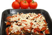 Pan of Eggplant Parmesan with Tomatoes in the Background — Stock Photo