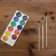 Palette with paint and brushes on  wooden table — Stock Photo #66164317