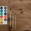 Palette with paint and brushes on the wooden background — Stock Photo #66229687