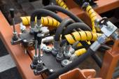 Hydraulic tubes, fittings and levers on control panel — Stock Photo