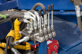 Hydraulic tubes, fittings and levers on control panel of mechani — Stock Photo