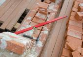 Mason bricklaying background with  level, hammer and  brick bloc — Stock Photo
