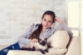 Girl with siamese cat relaxing in armchair — Stock Photo