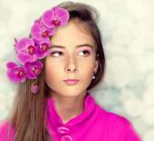 Young girl with long brown hair and orchid flowers — Stock Photo