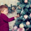 Boy decorates Christmas tree — Stock Photo #59823875