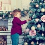Boy decorates Christmas tree — Stock Photo #59823877