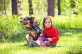 Girl with dog in summer garden — Stock Photo