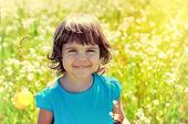 Happy little girl in walking in the flowers field — Stock Photo