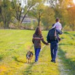 Happy family walking with dog — Stock Photo #81845046