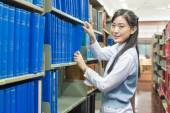 Young asain student picking a book from the bookshelf — Stock Photo