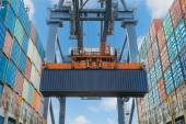 Shore crane lifts container during cargo operation in port — Stock Photo
