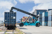 Forklift handling container box loading to freight train — Stock Photo