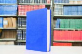 Blue book standing on table with bookshelf in background — Stock Photo
