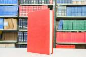 Red book standing on table with bookshelf in background — Fotografia Stock
