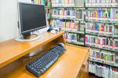 Computer in a library with many books and shelves in the backgro — Stock Photo