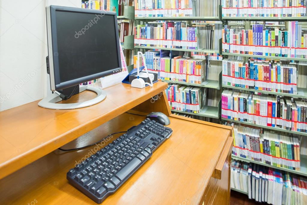 Computadora En Una Biblioteca Con Numerosos Libros Y