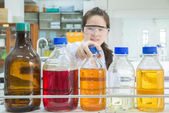 Asian scientist selecting bottle in shelf at laboratory (focus a — Stock Photo