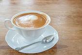 горячее молоко кофе искусства на деревянный стол — Стоковое фото