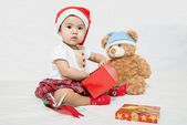 Asian baby with christmas cap pick up something in gift box — Stock Photo