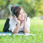 Asian student with Headphones Outdoors. Enjoying Music — Stock Photo #58228477