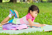 Young girl outdoors lying on the grass and drawing — Stock Photo