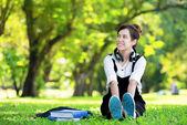 Female student girl outside in park listening to music on headph — Foto de Stock
