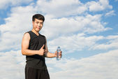 Asian fitness man holding water bottle and giving thumb up again — Stock Photo