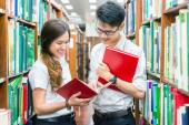 Asian couple of students in uniform at library — Foto de Stock