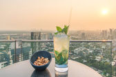 Mojito cocktail and cashews on table in rooftop bar — Stock Photo