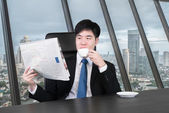 Businessman reading a newspaper while drinking coffee in his off — Stockfoto