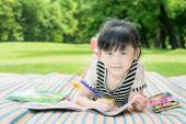 Asian girl kids outdoors lying on the grass and drawing — Stock Photo