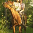 Loving young beautiful couple sitting on a horse and kissing at — Stock Photo #53506037