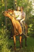 Loving young beautiful couple sitting on a horse and kissing at — Stock Photo