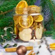 Christmas decoration. Fir tree, snow, candles, metal molds for Christmas cookies and jar with dried oranges, dried apples, cinnamon (selective focus) — Stock Photo #59726901