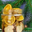 Christmas decoration. Fir tree, snow, candles, metal molds for Christmas cookies and jar with dried oranges, dried apples, cinnamon (selective focus) — Stock Photo #59726919