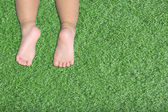Baby's feet on artificial turf — Stock Photo