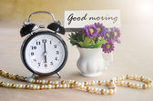 Alarm clock and Good morning tag with violet flower. — Stock Photo