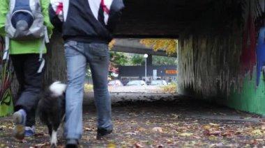 A couple holding hands walking through an underpass — Stock Video