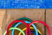 Colored plastic rings on the mosaic of the edge of a swimming po — Stock Photo